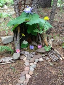Outdoor fairy house made of plants in front of tree