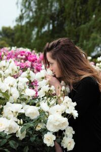 Yound woman in rose garden smelling white roses