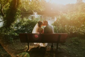 newlyweds kissing on park bench